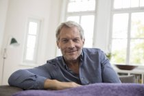 Portrait of mature man on the sofa at home — Stock Photo