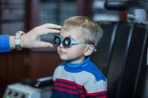 Boy doing eye test at optometrist in medical clinic — Stock Photo