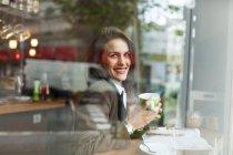 Lächelnde junge Frau in einem Café — Stockfoto