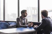Два бизнесмена разговаривают на пассажирской палубе парома — стоковое фото