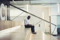 Businessman sitting on stairs using laptop — Stock Photo
