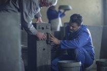 Рабочие вытирают объект на фабрике по производству травки — стоковое фото