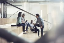 Young business people discussing, sitting on stairs — Stock Photo