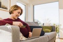 Lächelnde schwangere Frau auf der Couch Online-shopping — Stockfoto