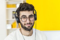 Portrait of smiling man with glasses and headphones — Stock Photo
