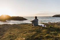 Frau sitzt bei Sonnenuntergang mit Surfbrett an der Küste — Stockfoto