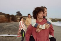 Young man carrying girlfriend piggyback on the beach — Stock Photo