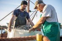 Pêcheurs Caucasiens professionnels travaillant sur chalutier — Photo de stock