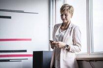Femme d'affaires à la fenêtre regardant le téléphone portable — Photo de stock