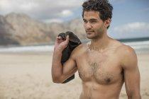 Молодий чоловік тримає ласти на пляжі — стокове фото
