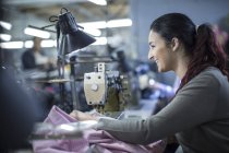 Seamstress in factory sewing clothes — Stock Photo