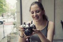 Улыбающаяся молодая женщина в кафе смотрит в камеру — стоковое фото