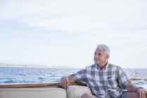 Homem sênior em uma viagem de barco, olhando a vista — Fotografia de Stock