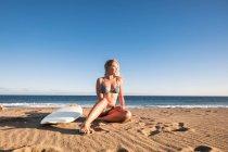 Молода блондинка серфер Іспанії, Тенеріфе, сидячи на пляжі — стокове фото