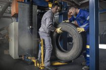 Two tire repairmen lifting tire in factory — Stock Photo