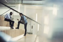 Empresario usando laptop y discutiendo con su colega - foto de stock