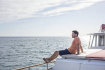 Young man sitting on a boat looking away — Stock Photo