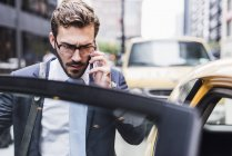 Businessman in Manhattan on cell phone entering a taxi, New York City, USA — Stock Photo