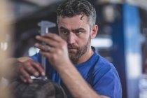 Mechaniker misst Lauffläche des Reifens in Werkstatt — Stockfoto