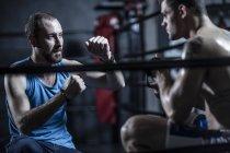 Treinador com pugilista jovem no ringue de boxe — Fotografia de Stock