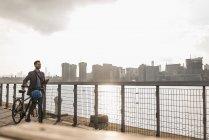 Homme d'affaires à vélo marchant le long d'East River, New York, États-Unis — Photo de stock