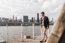Uomo d'affari che cammina lungo East River guardando il cellulare — Foto stock