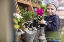 Boy with flower pot at garden centre — Stock Photo