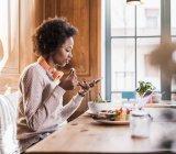 Junge Frau mit Handy in einem Café, während des Essens — Stockfoto