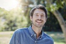 Retrato de homem sorridente caucasiano no parque — Fotografia de Stock