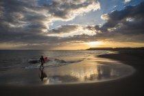 Далеких подання підліток хлопчик балансова для серфінгу на пляжі на гарний захід сонця — стокове фото