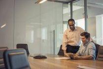 Deux hommes d'affaires souriants travaillent ensemble au bureau — Photo de stock