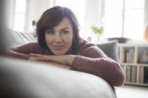 Portrait of woman lying on sofa at home and looking at camera — Stock Photo