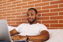Портрет молодого человека с наушниками на кровати с помощью ноутбука — стоковое фото
