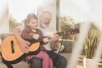 Großvater und Enkelin spielen gemeinsam Gitarre — Stockfoto
