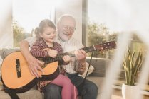 Дед и внучка, вместе играя гитара — стоковое фото