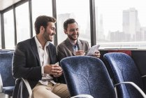 Two smiling businessmen with document talking on passenger deck of a ferry — Stock Photo