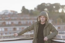 Man wearing hooded jacket standing on roof terrace — Stock Photo