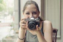 Ritratto di giovane donna sorridente che tiene una macchina fotografica — Foto stock