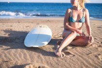 Young female surfer sitting on sandy beach and looking sideways — Stock Photo