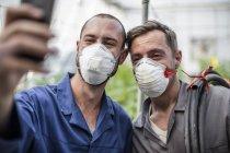 Jardineiros em estufa levando selfie usando máscaras faciais — Fotografia de Stock