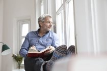 Relaxed mature man with book looking out of window at home — Stock Photo