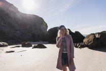 Blondes Teenager-Mädchen am Strand mit Handy — Stockfoto