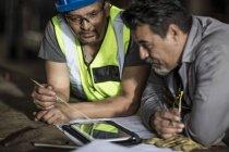 Ingénieurs discutant des plans de construction sur tablette numérique — Photo de stock
