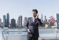 Бизнесмен, стоящий на пароме на Ист-Ривер с сотовым телефоном и наушниками, Нью-Йорк, США — стоковое фото