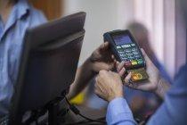 Customer using credit card reader at store — Stock Photo