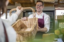 Smiling grocer serving customer in a farm shop — Stock Photo