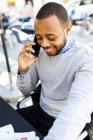 Smiling young man on cell phone at street cafe — Stock Photo