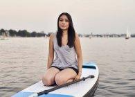 Germany, Hamburg, Young woman on paddleboard enjoying summer — Stock Photo