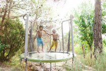 Boy jumping on trampoline while little brother splashing with water — Stock Photo