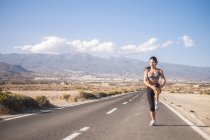 Young woman doing stretching exercises on empty road — Stock Photo